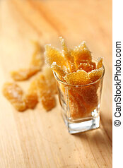 Caramelized stem ginger in a glass on wooden background