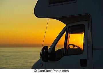 Caravan on coast at sunset
