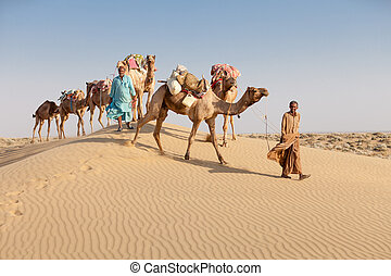 Caravan with bedouins and camels in desert - Caravan with...