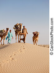 Caravan with bedouins and camels in desert