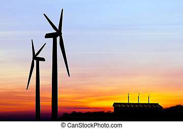 silhouette wind turbine generator with factory emissions of ...