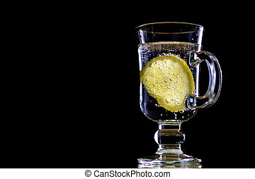 Carbonated drink in a glass bowl. Cool drink with bubbles and lemon.