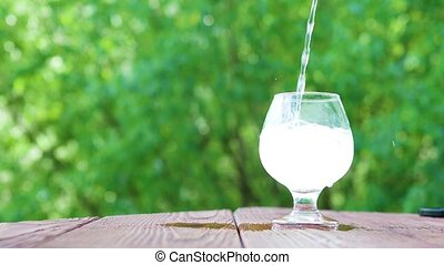carbonated mineral water pours into a glass blurred tree leaves in the background, concept of healthy life