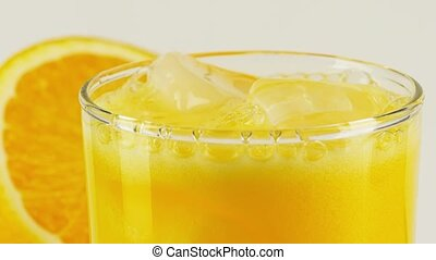 Carbonated orange soft drink with ice in a glass, close-up ...