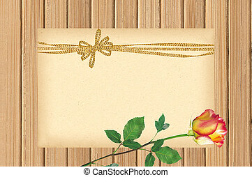 Card decorated with golden bow and beautiful rose on wooden background