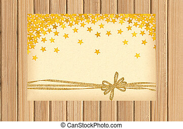 Card decorated with golden bow and stars on wooden background