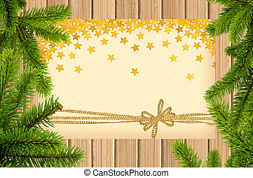 Card decorated with golden bow and stars on wooden background with christmas tree branch