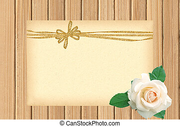 Card decorated with golden bow and white rose on wooden background