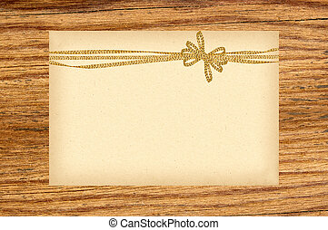 Card decorated with golden bow on wooden background