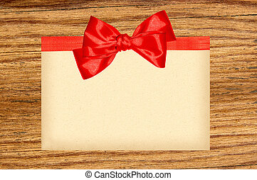 Card decorated with red ribbon and bow on wooden background