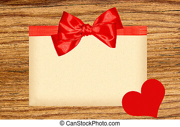 Card decorated with red ribbon, bow and heart on wooden background
