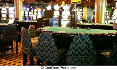 card table of empty casino and slot machines behind
