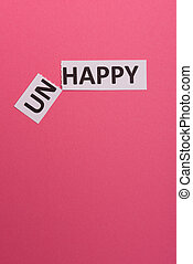 card wit text unhappy, cutting word 'un' so it written 'happy'. Copy space. Lime background. Studio shoot