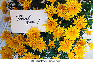 "card with handwritten text ""thank you"" on a background of flowers"