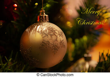 Card with merry christmas greeting text and golden ball.