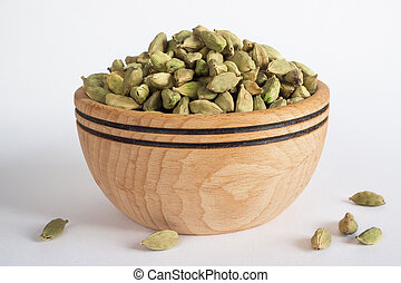 Cardamom in a wooden bowl. Close up.