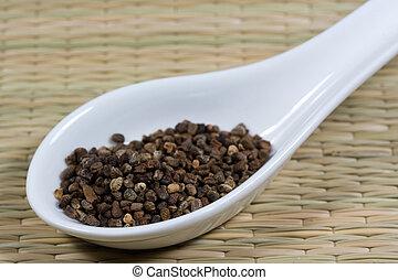 cardamom on a white spoon