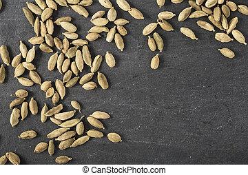 Cardamom Seeds - Cardamom seeds spread on slate surface with...