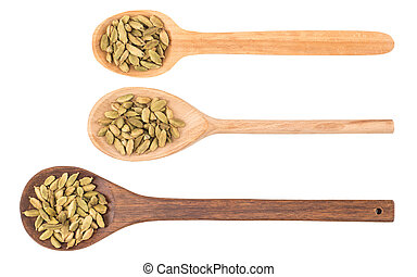 Cardamom seeds in the wooden spoon on white background