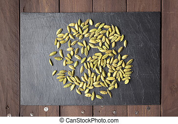 Cardamom seeds scattered on a slate plate
