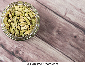 Cardamom spice in a mason jar over weathered wood background