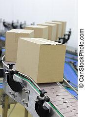Cardboard boxes on conveyor belt in factory