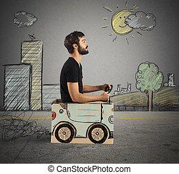 Cardboard car in drawing city - Boy driving cardboard car in...