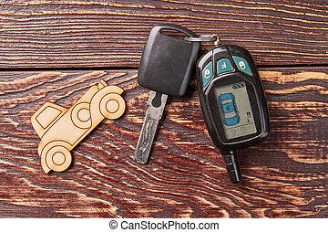 Cardboard car, key, wooden table.