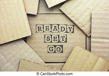 Cardboard card with words Ready Set Go made by black alphabet stamps