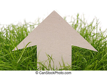 cardboard direction sign on green grass