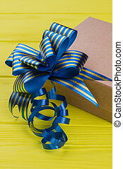 Cardboard gift box with blue striped ribbon bow knot.