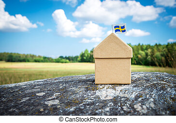 Cardboard house with Swedish flag on a mossy rock