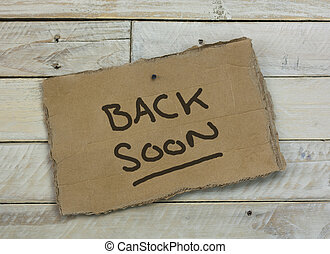Cardboard sign on a wooden background