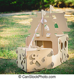 Cardboard toy boat in the park.