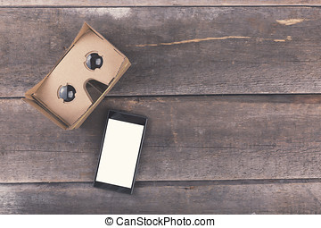 cardboard virtual reality glasses with blank smartphone on wooden background