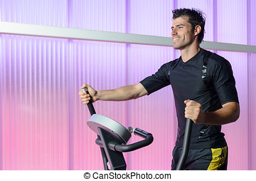Cardio in Elliptical - Handsome man doing cardio with...