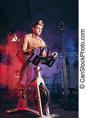 Cardio Workout. Shirtless man training on bicycle, cycling mashine in gym