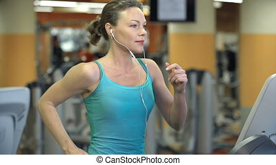 Cardio Workout - Side view of woman running in a gym and...