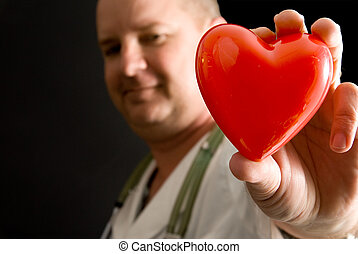 A doctor holding a heart shaped object.