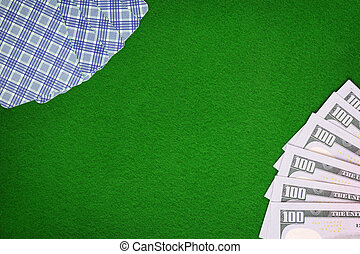 Cards and dollars on green casino felt table