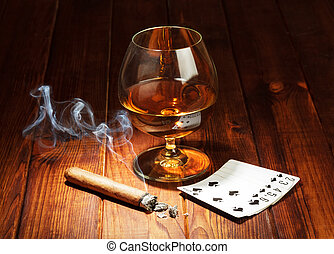 Cards, cigar and glass of whisky on wooden table