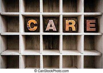 "The word ""CARE"" written in vintage ink stained wooden letterpress type in a partitioned printer's drawer."