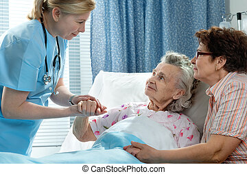 Doctor talking to elderly patient lying in bed in hospital