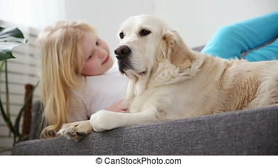 care for pets. A blonde girl strokes her dog with love in the living room. happy golden retriever in the family.