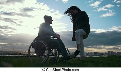 Care of disabled - man in a wheelchair with woman talking at the cloudy sunset