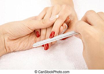 Care of nails - Close up of grinding nails a nail file,...
