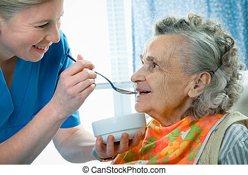 Care - senior woman 90 years old being fed by a nurse