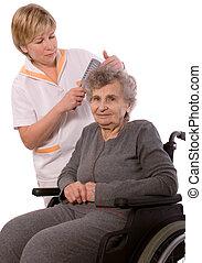 care - Nurse dressing the hair of a senior woman