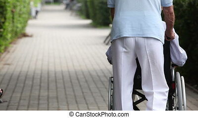 Care - Caring senior man pushing his wife's wheelchair along...
