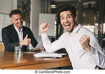 Career, office and placement concept - excited caucasian man 30s rejoicing and clenching fists after job interview, since was hired for a job in big company